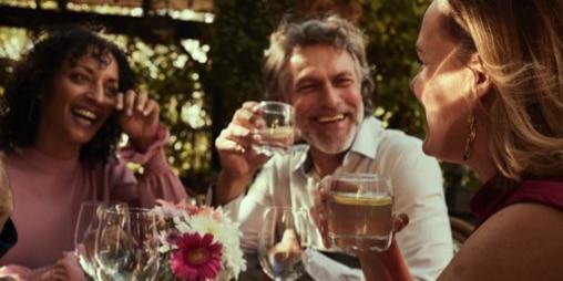 Дві жінки та чоловік сміються на вечірці в літньому саду.