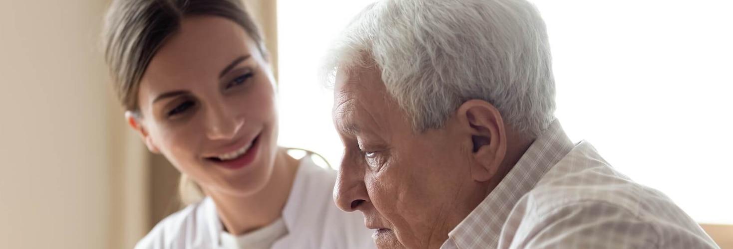 Pflegerin und älterer Patient bei Stuhlinkontinenz-Beratungsgespräch