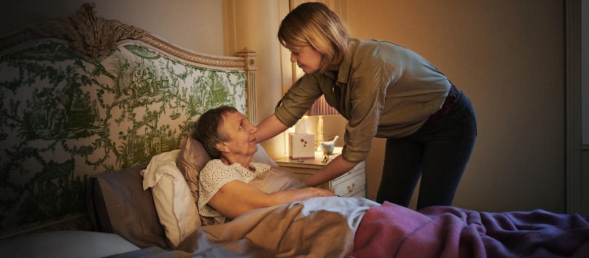 Kobieta pomaga starszej osobie leżącej w łóżku