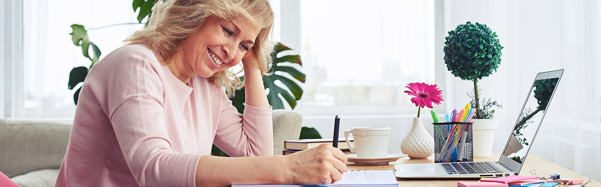 Woman smiling and writing