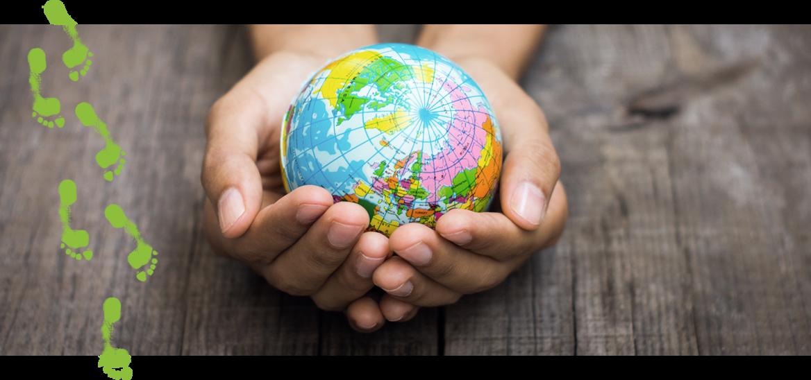 Hænder der holder en lille globus i mange farver.