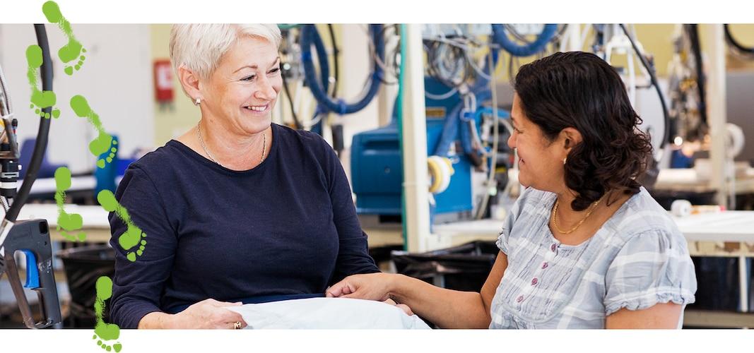 Två leende kvinnor på en produktionsanläggning tillhörande TENA, undersöker en absorberande produkt.