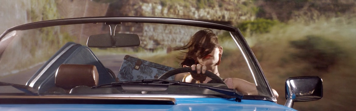 Woman driving cabriolet with hair in face.