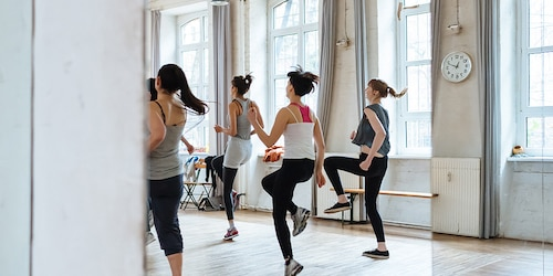 Quatre personnes suivant un cours de step, vues de dos.
