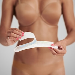 A woman releasing the paper from TENA Discreet Normal