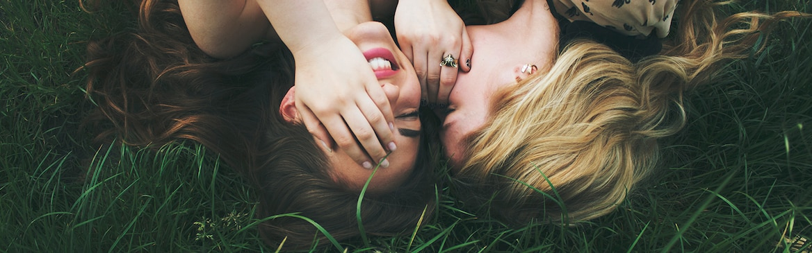 Two girls lying on the grass laughing.