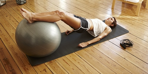 Woman doing pilates workout with ball wearing TENA incontinence products