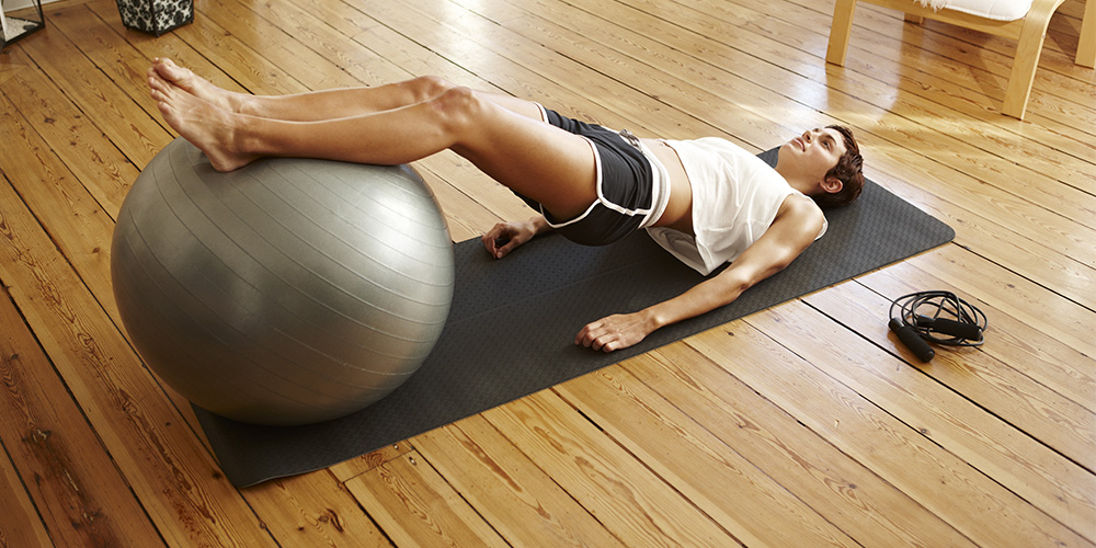 1000x500_woman_laying_on_pilates_ball.jpg