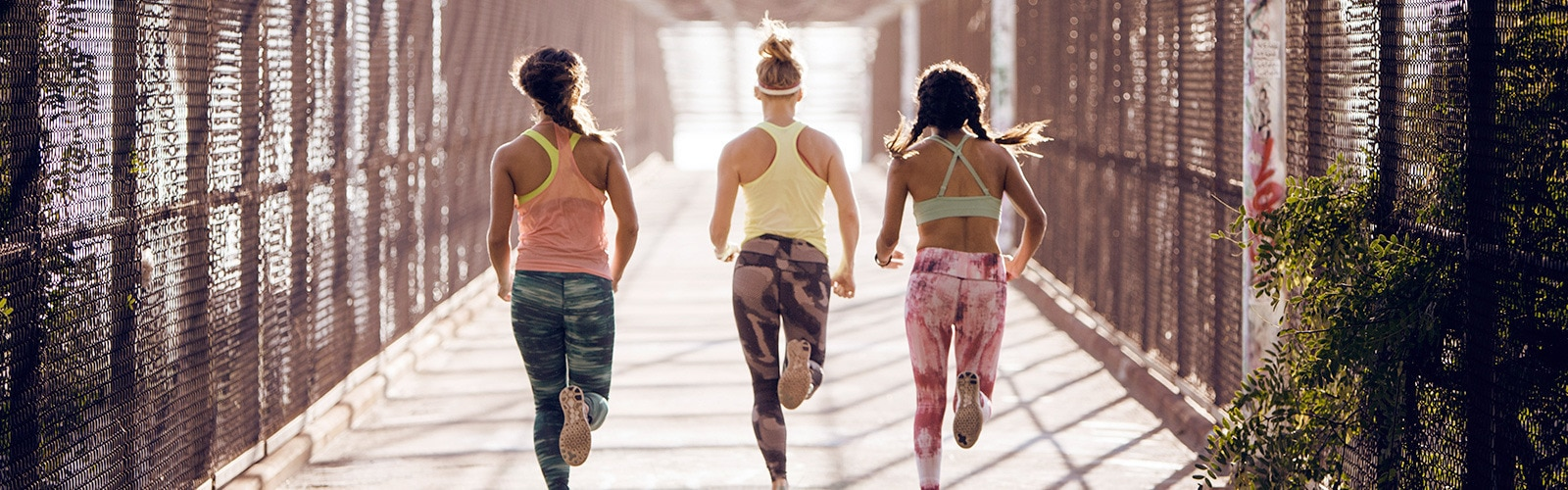 Three women running seen from behind