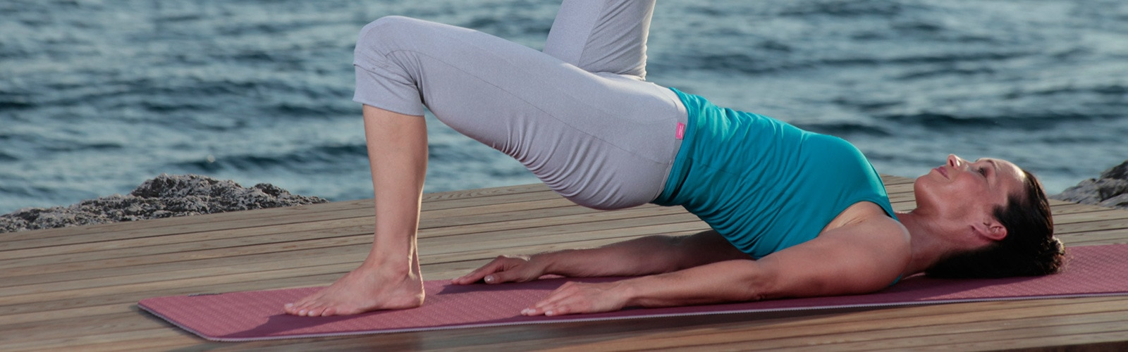 Woman doing yoga by the sea.