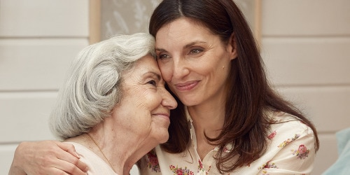 Jongere vrouw die oudere vrouw omhelst – ontdek hoe TENA-producten de beste zijn voor uw naaste