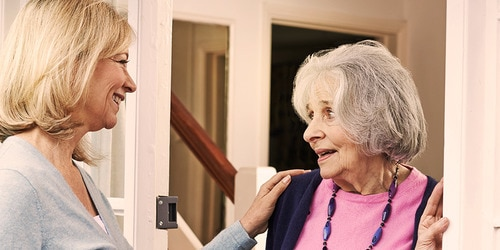 Younger woman greeting an older woman