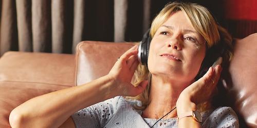Vrouw die zich ontspant en naar muziek luistert – tips hoe u als verzorgende minder stress hebt
