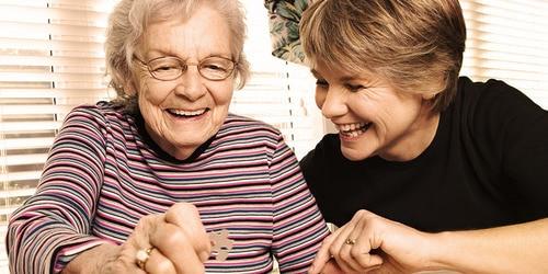 Senhora jovem e senhora mais velha a fazer um puzzle – atividades que pode fazer com o seu ente querido