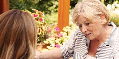 Starejša gospa sedi z mlajšo žensko – zagotavljanje cenovno ugodne nege za vaše bližnje