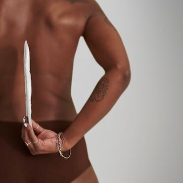 Bild einer schwarzen Frau, die eine TENA Discreet Einlage hinter dem Rücken hält und zeigt, wie dünn diese ist.