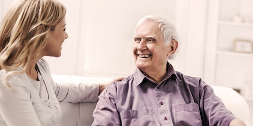 Older man sitting with younger woman indoors
