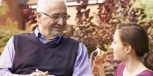 Older man sitting with younger woman outside