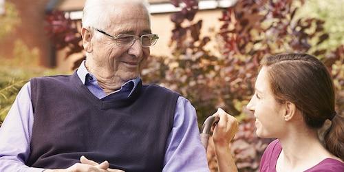Starejši moški sedi zunaj z mlajšo žensko – preberite o izkušnjah drugih negovalcev