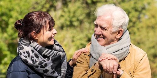Starší muž sedí vonku s mladšou ženou – finančná pomoc pre opatrovateľov