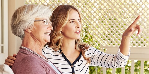 Elderly woman and younger woman talking outside