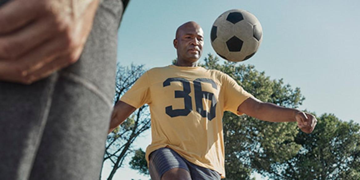 bir erkek açık alanda futbol oynuyor