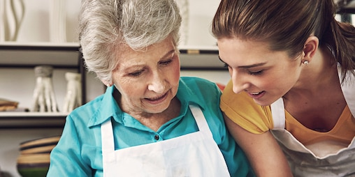 Elderly woman in an apron with younger woman in an apron