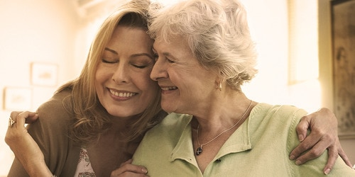 Elderly woman hugging younger woman