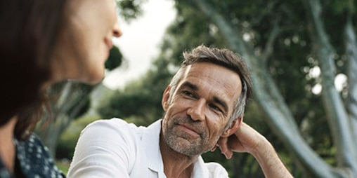 mature man with beard and white shirt looking at a woman