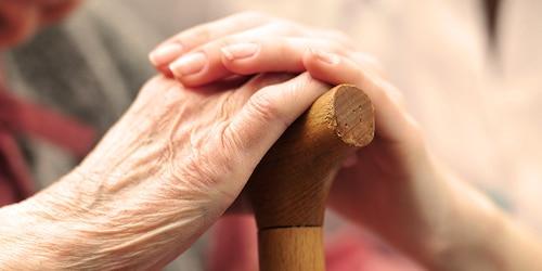 Žena v seniorskom veku sa drží za ruku s mladšou ženou – podpora miestnych organizácií a charity