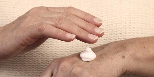 Ältere Frau trägt einen Feuchtigkeitsspender auf – bewahren Sie die Hautgesundheit Ihres Angehörigen