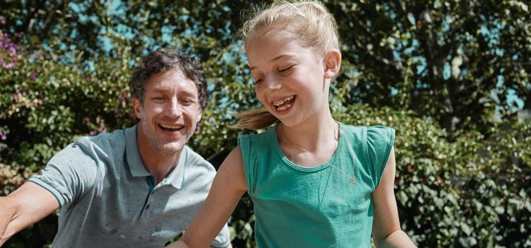 Vater spielt mit seiner Tochter Basketball.