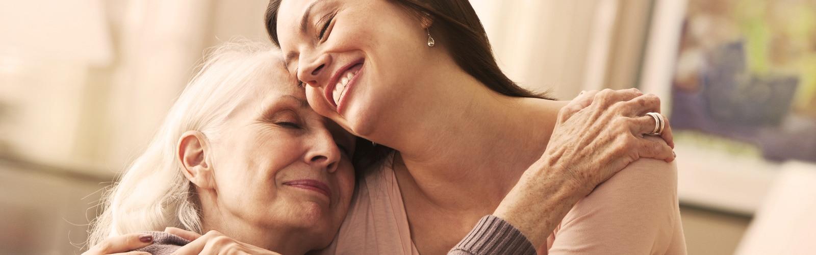 Jeune femme étreignant une femme âgée – comment gérer la dégradation de l'état général de santé de votre proche.