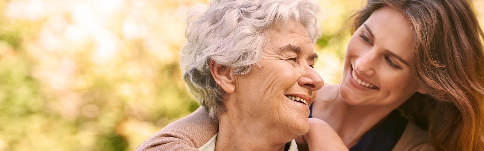 Mladá žena objíma staršiu ženu – pochopenie typu inkontinencie, ktorý sa prejavuje u vašej milovanej osoby