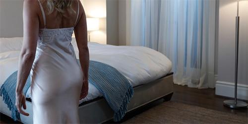 Frau im Nachthemd, die gerade ins Bett geht.