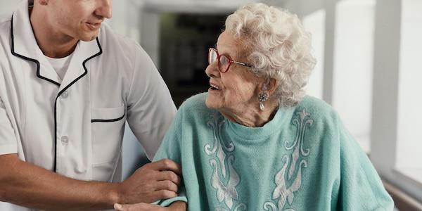 Ältere Dame mit Pflegekraft im Gang