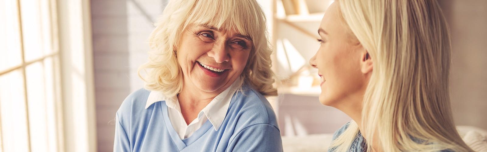 Femme âgée riant avec une femme plus jeune – Les différentes façons d'aider votre proche à gérer son incontinence
