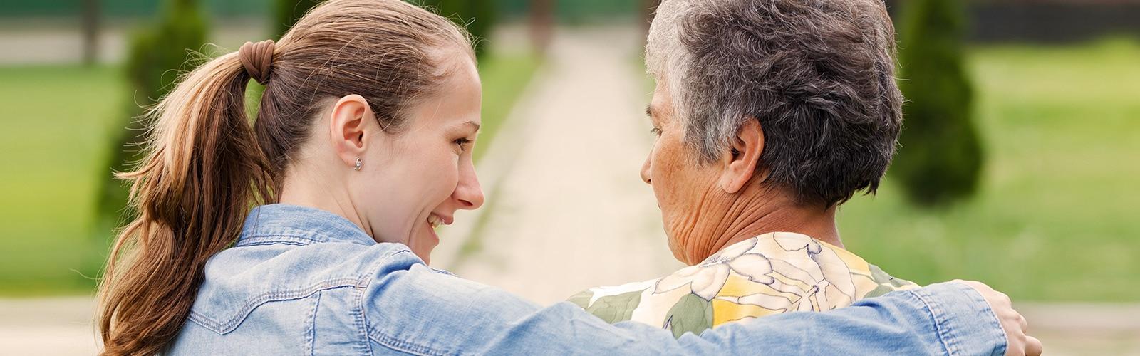 Starejša gospa sedi zunaj z mlajšo žensko – načrtujte nego