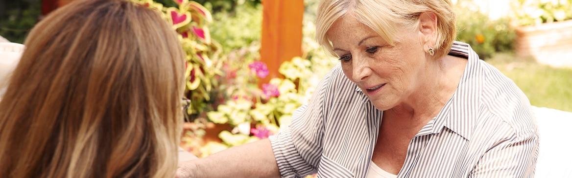 Mujer mayor sentada con mujer joven: ofrecer una atención poco costosa a tu ser querido