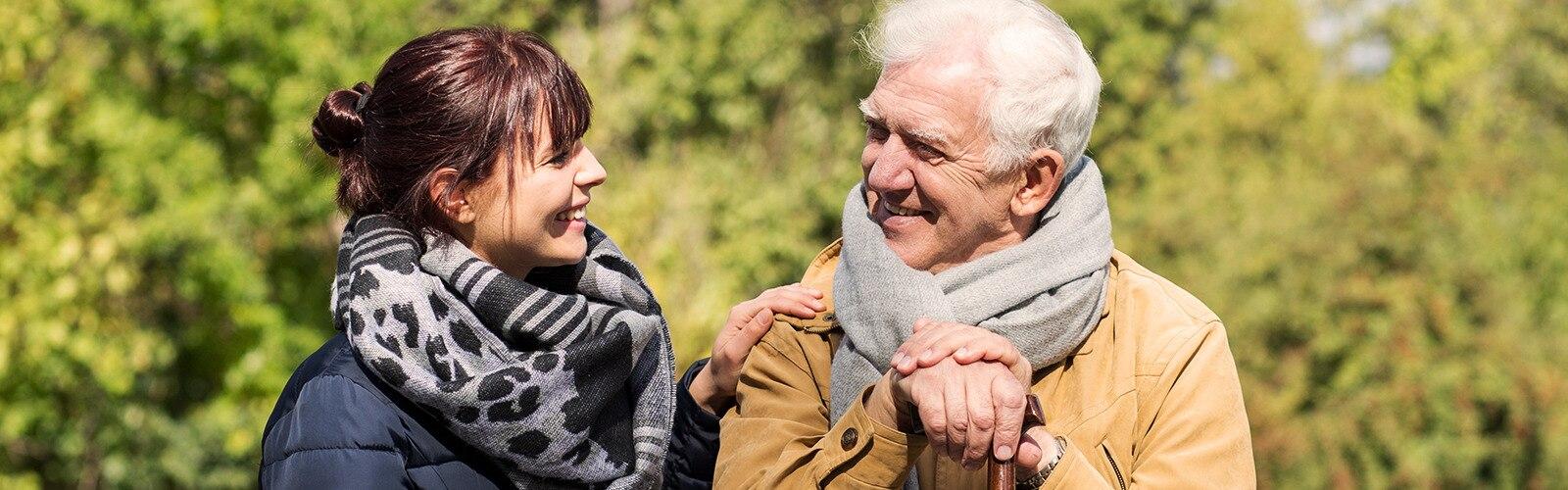 Starejši moški sedi zunaj z mlajšo žensko – finančna pomoč za negovalce.