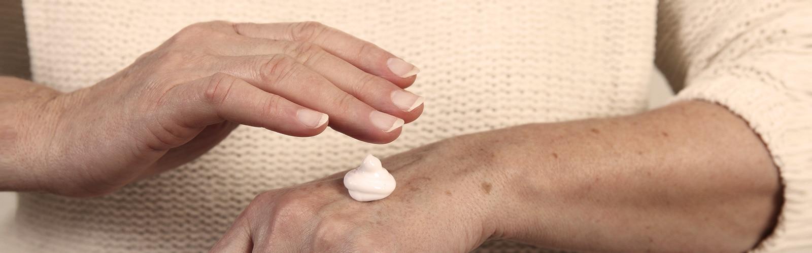 Elderly woman applying moisturizer