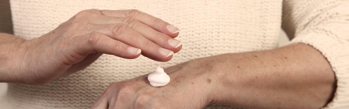 Starsza kobieta nakładająca balsam nawilżający – dbaj o zdrowie skóry swoich bliskich