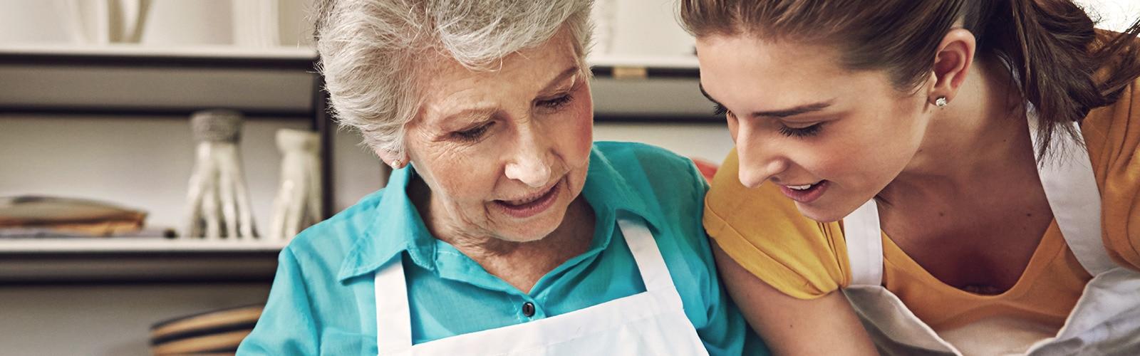 Žena v seniorskom veku pečie s mladšou ženou – odpovede na najčastejšie otázky o opatrovateľstve