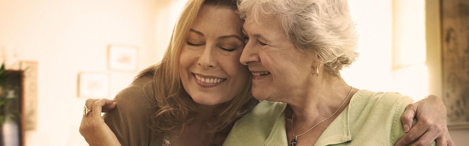 Žena v seniorskom veku objíma mladšiu ženu – príprava na úlohu opatrovateľa