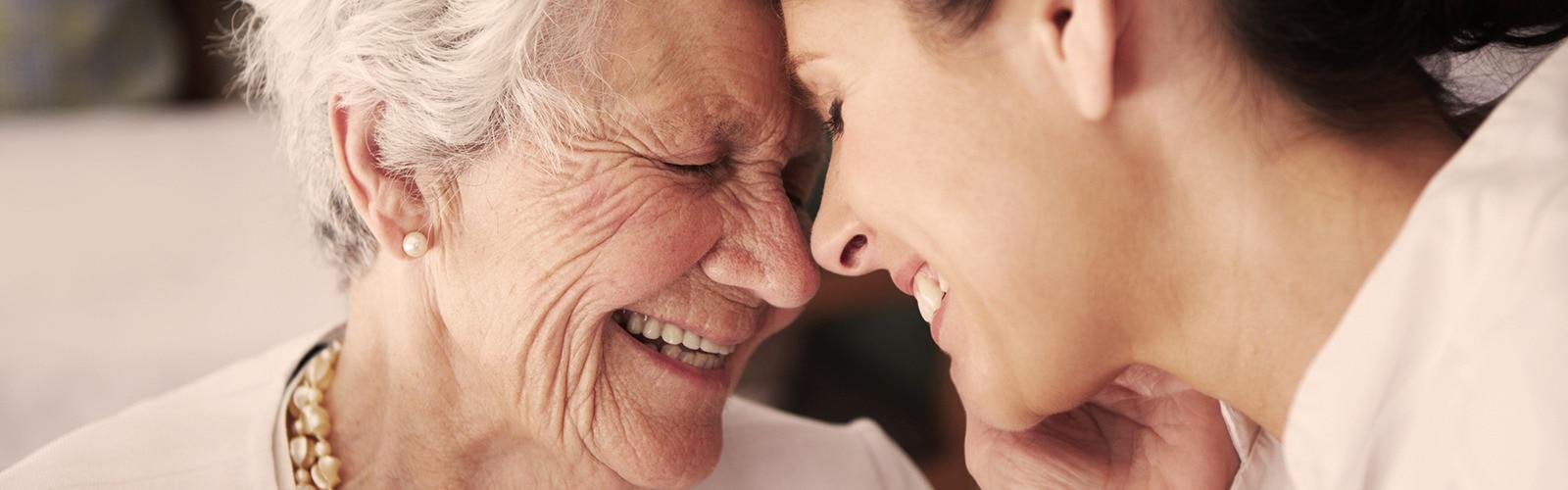 Una donna anziana e una più giovane ridono insieme – Storie di altri caregiver