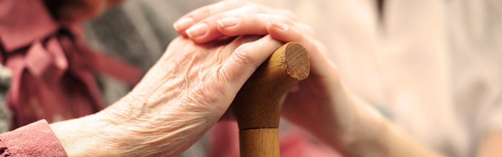 Pagyvenusi moteris, laikanti rankas su jaunesne moterimi