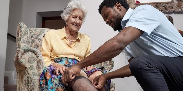 Una signora anziana si fa aiutare a indossare le calze