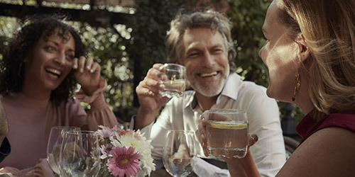 2 women and mature man laughing and drinking wine outdoors