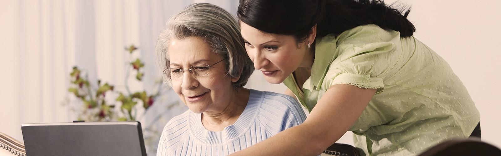Idős nő egy fiatal nővel együtt számítógépezik – Így hat az Alzheimer-kór szeretteinkre