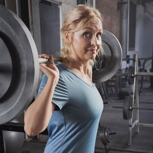 Confident woman standing in gym with heavy weights on her shoulders